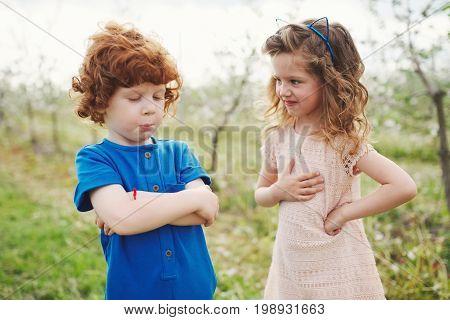 happy little boy and girl in blooming garden