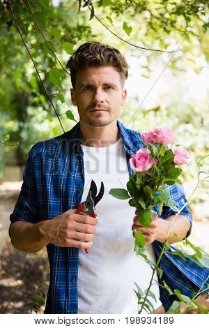 Portrait of man trimming flowers with pruning shears in garden on a sunny day