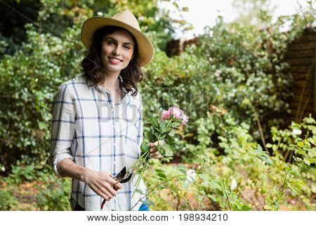 Portrait of woman trimming flowers with pruning shears in garden on a sunny day