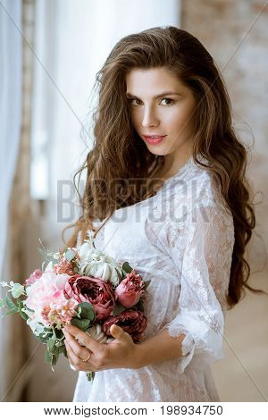 Fashionable female portrait of cute lady in white robe indoors. Close up beautiful sexy model girl in elegant pose. Closeup beauty brunette woman with hairstyle and bouquet. Glamorous face with makeup