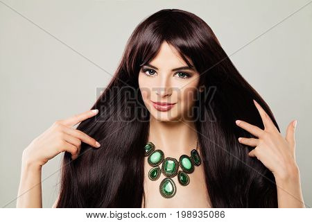 Cute Model Woman with Makeup and Long Brown Hair Touching her Hand her Hair