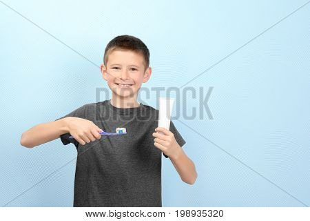 Cute boy with toothbrush and paste on color background. Teeth cleaning concept
