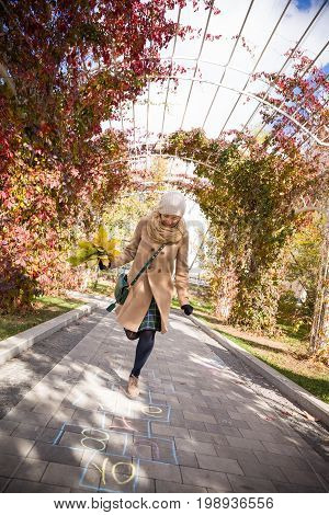 Happy young woman dancing in the park in an autumn sunny day.Girl enjoying walking in the park and holding yellow leaves. Woman with bunch of leaves running outdoors.