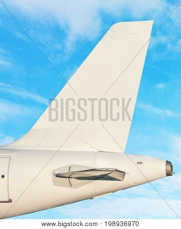 Airplane tail fin - sky with white clouds in background