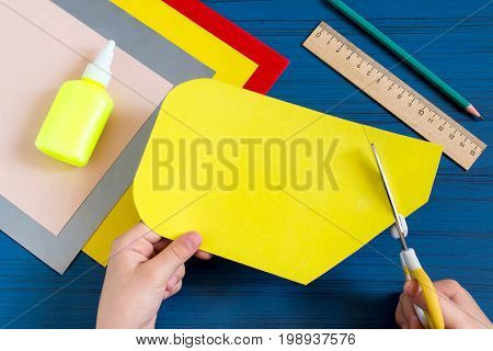 Making greeting card in form of pencil for new school year. Welcome back to school. Children's art project. DIY concept. Step-by-step photo instruction. Step 4. Child cuts out card in form of pencil