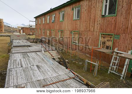 PYRAMIDEN, NORWAY - SEPTEMBER 03, 2011: Exterior of the deserted wooden building at the abandoned Russian arctic settlement Pyramiden, Norway.