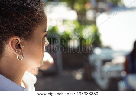 Close-up of waitress with ears piercing looking away