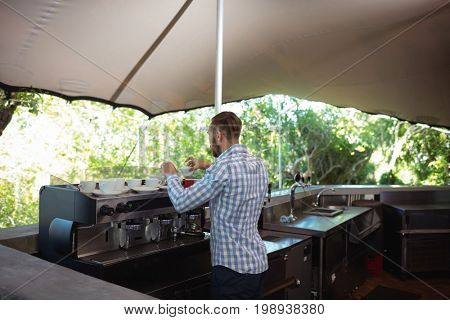 Rear view of waiter preparing coffee at outdoor café