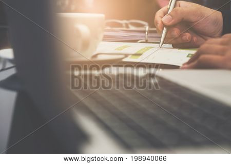 Close Up Shot Of A Man's Hand Holding A Ball Point Pen On The Turnover Document Report On Desk With
