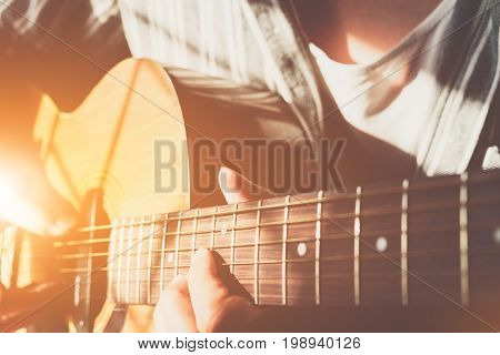 close up shot of strings and guitarist hands playing guitar over black - selective focus with vintage filter