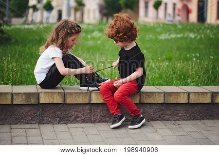cute boy helps little girl tie shoelaces