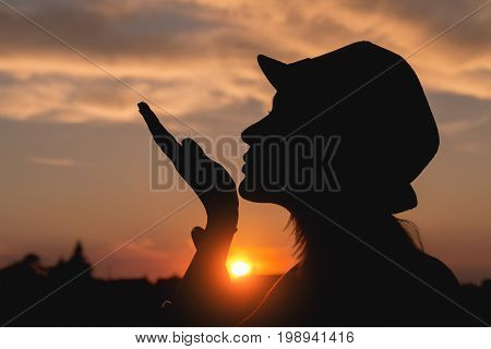 Sillhouette of a young girl enjoying in the sunset / sunrise.