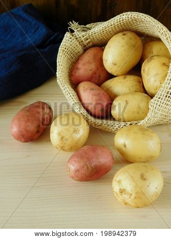Potatoes are scattering out of a sack on a wooden table