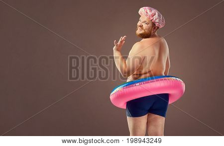 Fat funny man in a swimsuit with an inflatable circle.  Humor, freak, comedian.