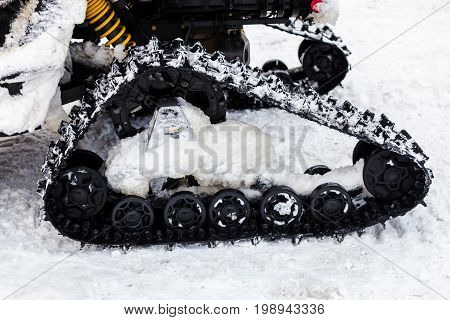 Close up photo of snowmobile caterpillar treads in the snow shallow DOF