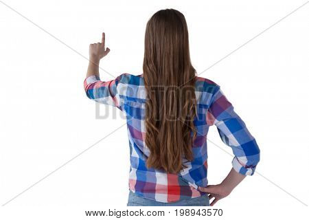 Rear view of girl pressing an invisible virtual screen against white background