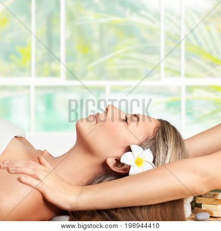 Beautiful blond woman lying down on massage table in spa salon, enjoying facial massage, doing facial mask, healthy lifestyle and beauty treatment concept