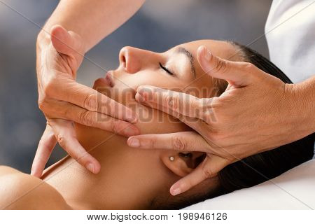 Close up portrait of woman having facial cosmetic therapy. Therapist applying cream on female cheek.