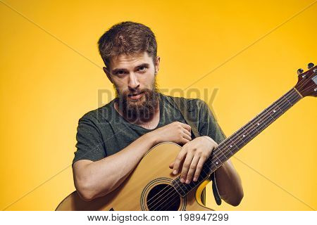 A man with a beard holds a guitar on a yellow background, a musician.
