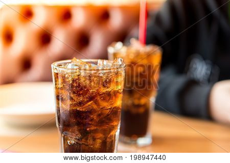Double soft drink carbonated fresh food soda white dish on wooden table with handsome man sitting brown sofa in pizzeria restaurant