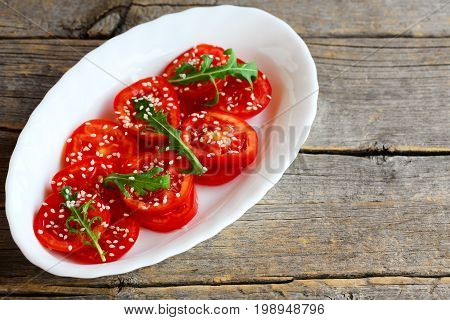 Salad with fresh tomato, rucola, sesame seeds and vinaigrette dressing on a white plate isolated on an old wooden background with copy space. Healthy dish for breakfast, lunch and dinner. Rustic style