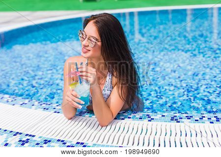 Tenned Beautiful Woman In Blue Bikini And Sunlasses Sitting In Swimming Pool With Cocktail. Fashiona