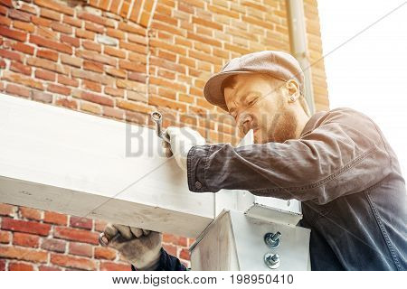 A strong man builder in dark construction overalls and a gray cap builds a house from a wooden beam painted white on a summer day in the background a brick building