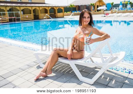 Happy Young Woman With Cocktail Laying On Chaise Lounge. Time Summer Photo.