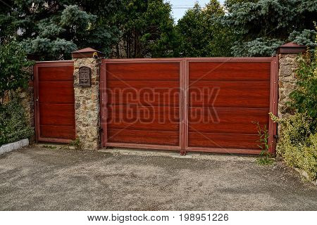 Red wooden gate and closed gate on a stone fence with a mail box