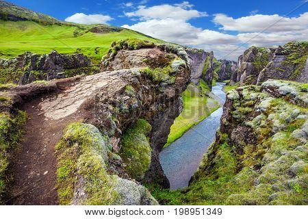 The striking canyon in Iceland. The concept of active northern tourism. Bizarre shape of cliffs surround the stream with glacial water. The Icelandic Tundra in July