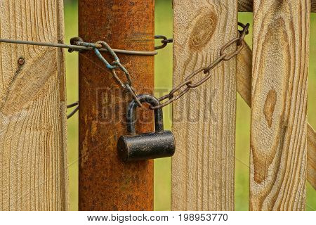A large old padlock and chain on a pipe and a wooden board