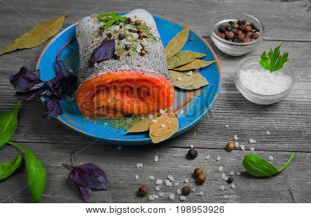 Preparing Pickling red fish fillet of salmon steak rolled on blue plate, gray wooden background. Ingredients for cooking fillet of salmon basil, pepper, salt, bay leaves, spices for Pickling red fish.