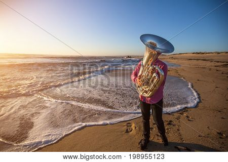 Musician playing the Tuba on the sea coast. Musical instrument. Romantic photo.