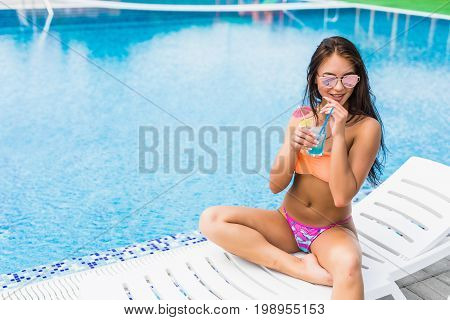 Enjoying Summer. Beautiful Young Woman In Blue Sexy Bikini Drinking Cocktail While Relaxing In Deck