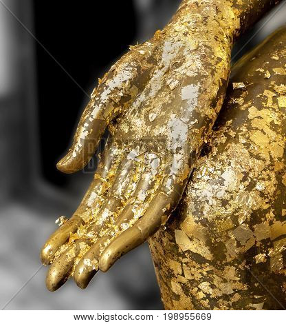 Gold leaf stick on Fingers of Buddha statue.