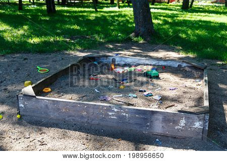 Abandoned sandbox with broken toys in forest