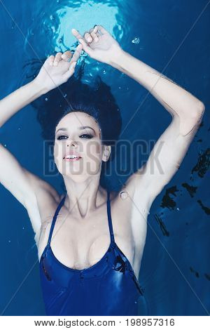 Beautiful brunette woman in a blue swimsuit inr the pool. Portrait of a beautiful woman with long hair. Woman in the pool. Girl with wet hair.