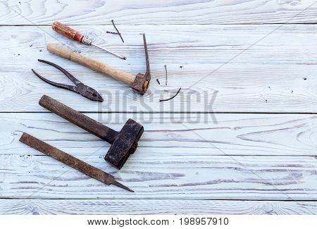 Vintage hammers, pliers, screwdriver, rasps and nails on a wooden background close-up