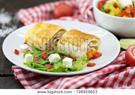 Lavash Rolls With Meet, Vegetables And Cheese Served With Green Lettuce Salad, Feta Chesse And Red P
