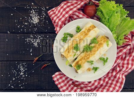 Lavash Rolls With Meat, Vegetables And Cheese Served With Green Lettuce Salad On Rustic Wooden Table