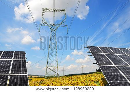 Solar panels with electricity pylons in sunflower field. Concept of sustainable resources.