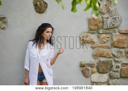 Young girl wearing white t-shirt and jeans. Concrete wall background