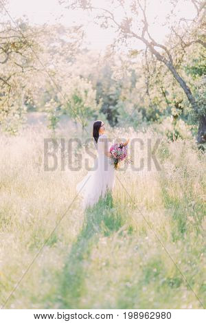 Back photo of the bride looking behind and holding the big bouquet of the flowers in the middle of the field