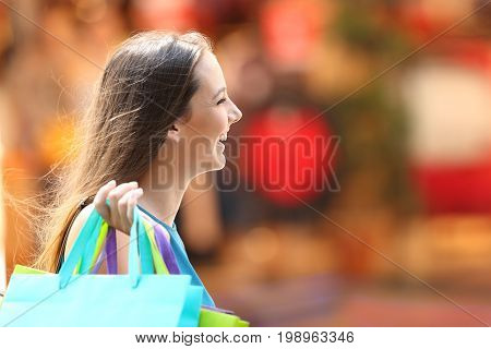 Side view portrait of a happy shopper shopping walking on the street