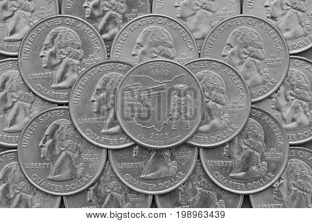 Ohio State and coins of USA.Pile of the US quarter coins with George Washington and on the top a quarter of Ohio State.