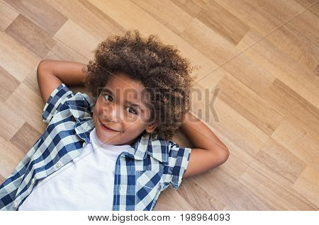 Playful little boy with curly hair lying on wooden floor and think. Top view of shy african kid looking at camera with copy space. Pensive black boy lying at the floor with hands behind the head.