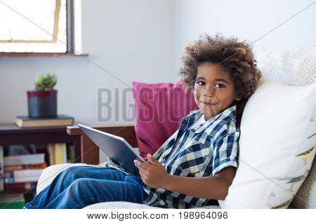 Young african child sitting on sofa playing game on a digital tablet. Cheerful little black boy holding digital tablet at home. Happy smiling kid using digital tablet and looking at camera.