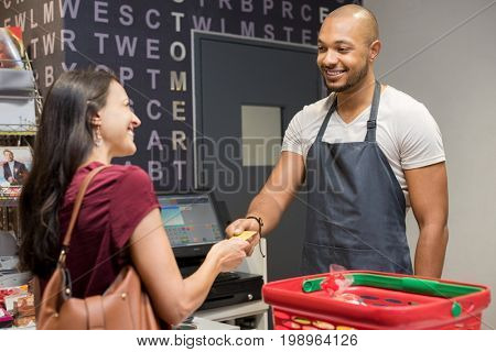Happy woman at checkout of grocery store paying with credit card to cashier. Smiling woman paying with her EC card at supermarket. Mature woman at cash register paying with credit card to man.