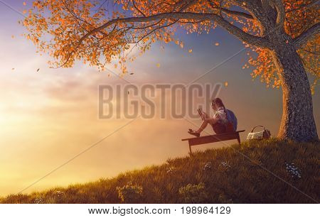 Back to school! Happy cute industrious child reading the book near tree on background of sunset. Concept of successful education and reading.