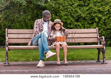Adorable African American Grandchild And Her Grandfather Listening Music On Digital Tablet While Sit